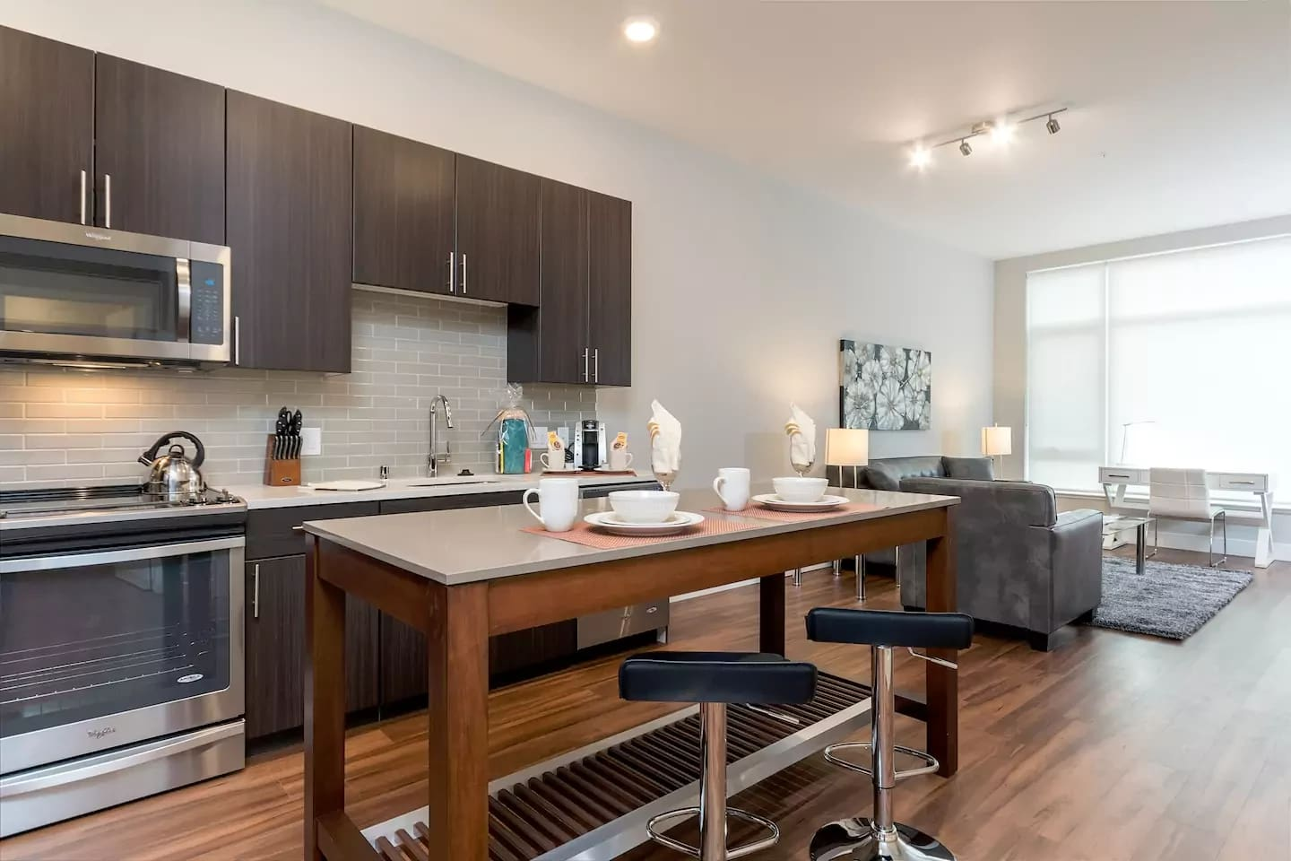 Fully equipped kitchen with stainless steel appliances, pots, pans and dishes