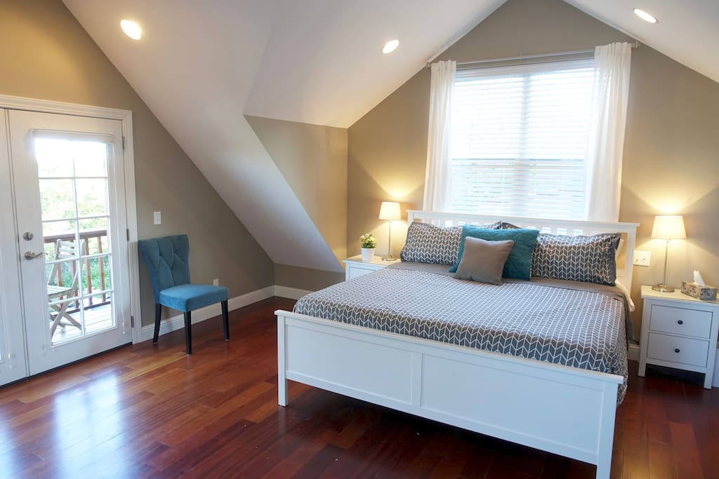 Spacious Master Bedroom with balcony views, TV, sofa, a King Sized bed with memory foam soft-top mattress, desk, closet space, and cathedral ceilings.