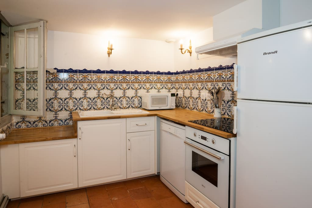 Charming French kitchen with white cabinets and wood countertops in a historic 1600's Carcassonne vacation rental. #Frenchkitchen #classic #France #apartment