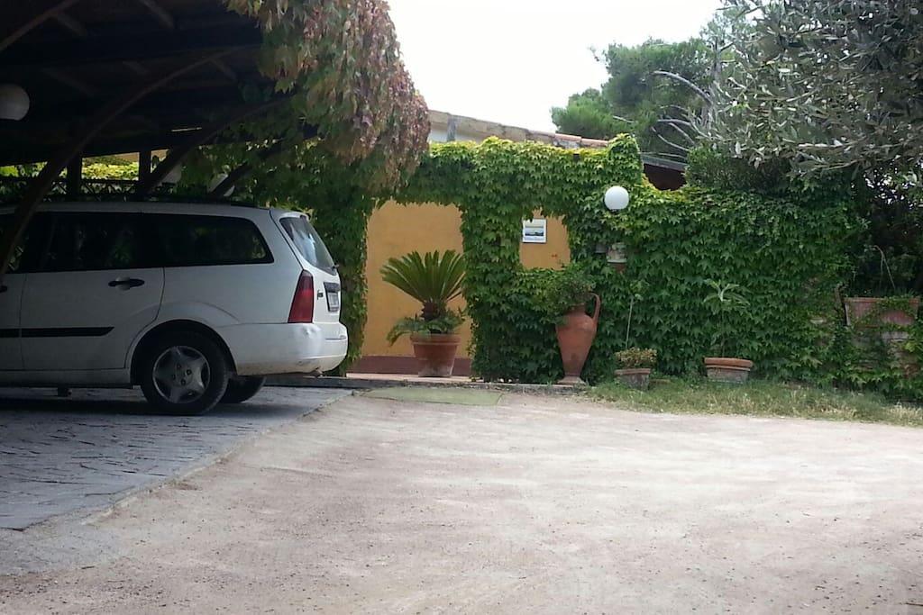 Ingresso alla proprietà con parcheggio privato con posti auto coperti. Our Private Parking Area.