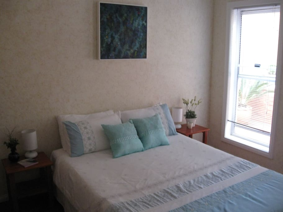 one of two sunny queen size guest bedrooms