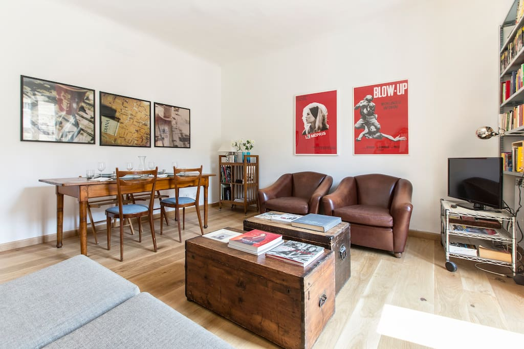 living room with sofa bed, two antique armchairs, table for 6