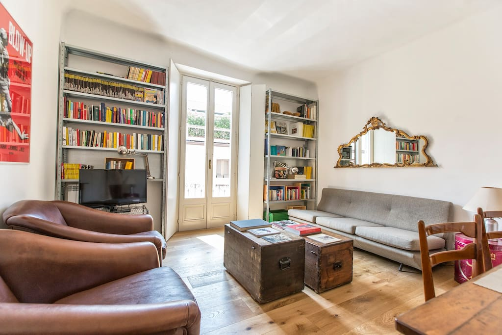 living room with sofa bed, two antique armchairs, table for 6, small balcony