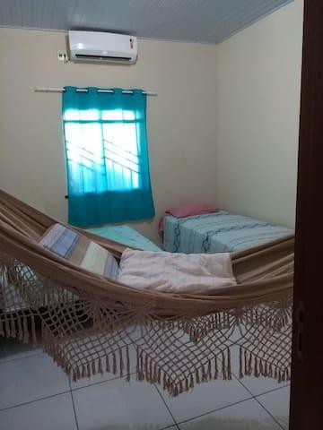 quarto com central de ar de 12btu,, uma cama de casal uma cama de solteiro um colchão e uma rede