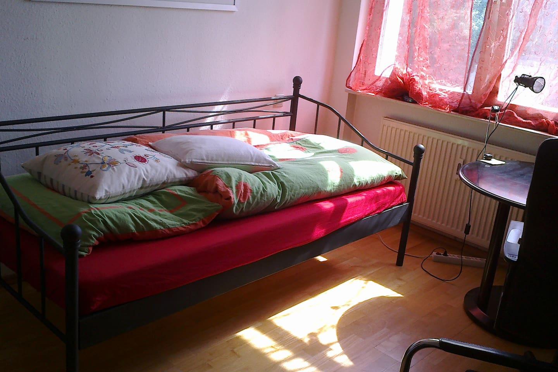 Zimmer mit Bett, Schreibtisch mit Bürostuhl, runder kleiner Esstisch, Kleiderschrank, Regal, angenehmer Beleuchtung