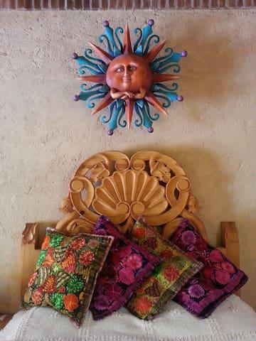 Casa Amor está llena de detalles. Por ejemplo, su confortable cama matrimonial, tiene acabados muy bonitos en su cabecera, acompañada además de los folclóricos textiles mexicanos en sus cojines.