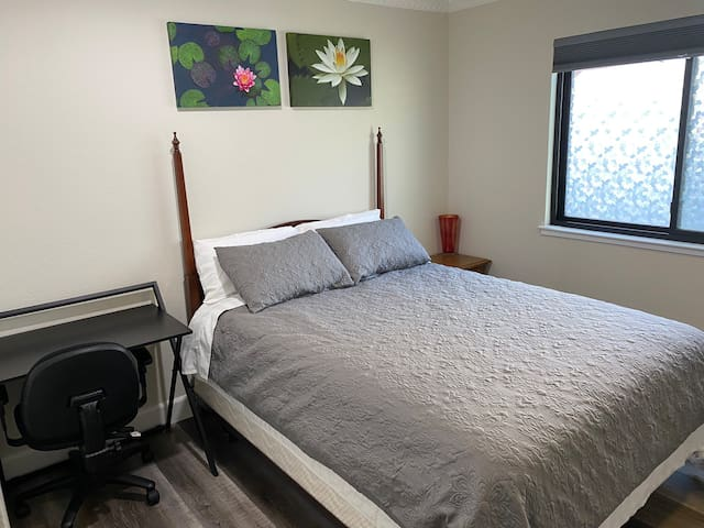 Private bedroom with queen sized bed, closet, and a desk
