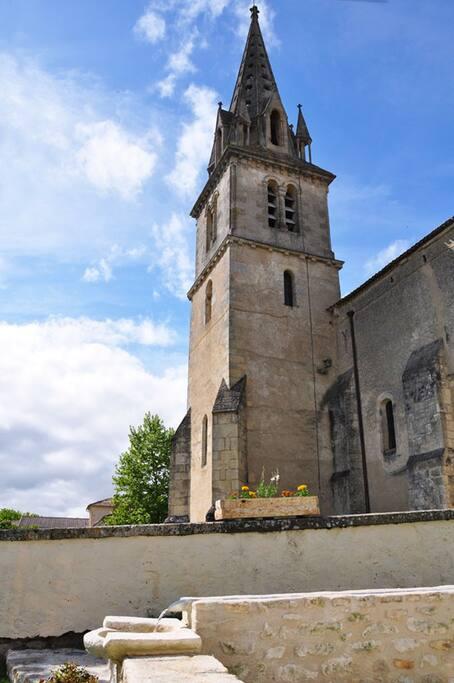 Vue du clocher en sortie du gîte, avec la fontaine.