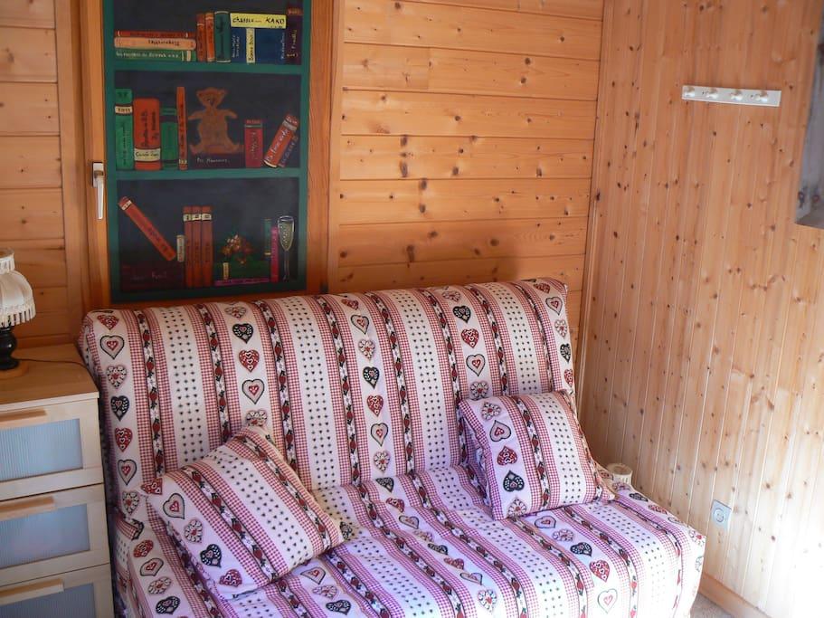 une chambre ou un coin lecture avec une porte fenêtre ouvrant sur les sapins