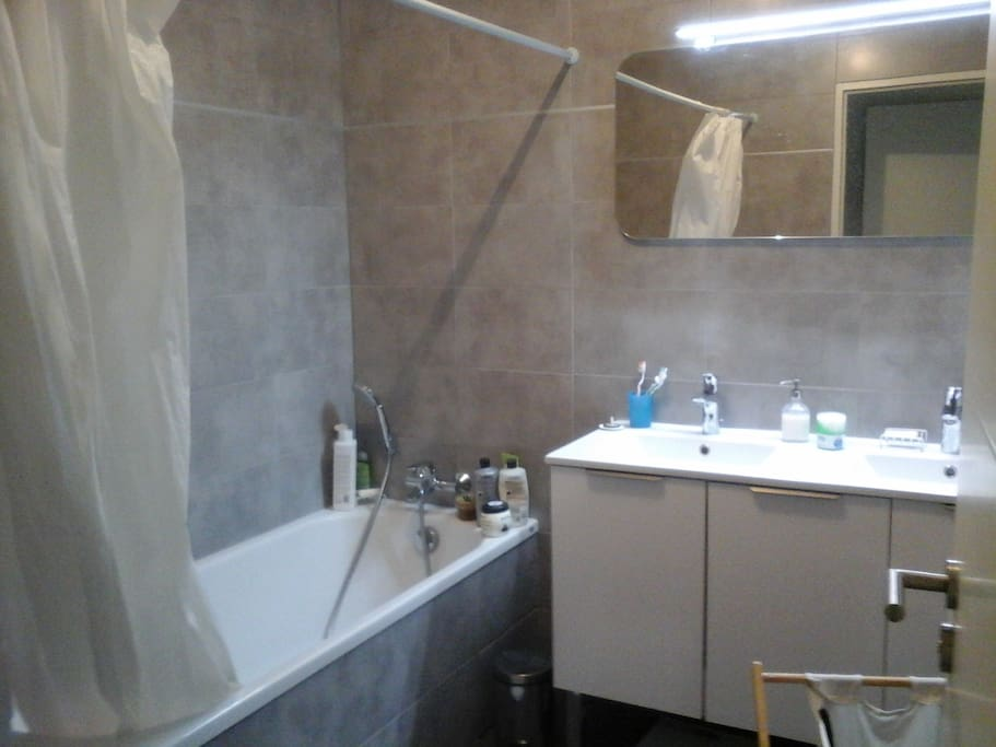 salle de bain avec deux lavabos et une machine à laver.