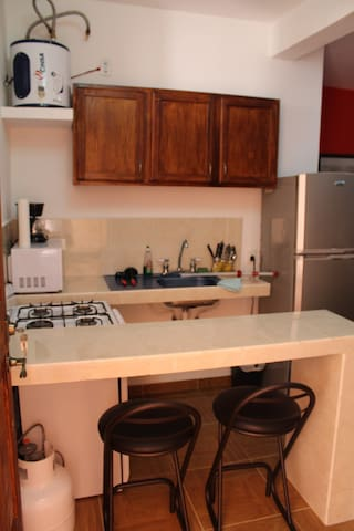 Kitchen with microwave, gas stove, refrigerator, glasses, pots, pan, plates and basic utilities.