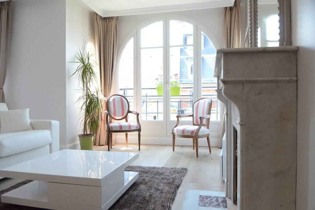 Living room with antique marble fireplace. South facing so extremely sunny