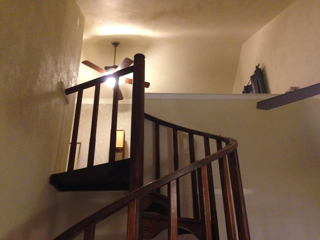spiral staircase to lofted bedroom, closet, small dresser