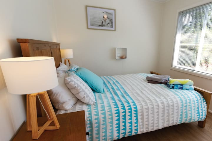 The front bedroom - queen size bed. Faces the front garden, flooded with afternoon sunlight. Quality linen, towels and beach towels provided. Large wardrobe with sliding doors in this room - plenty of storage.