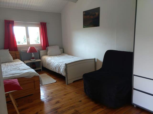 La Chambre avec 2 lits simples et 1 fauteuil BZ 1 place, 1 armoire de rangement, une table de chevet.