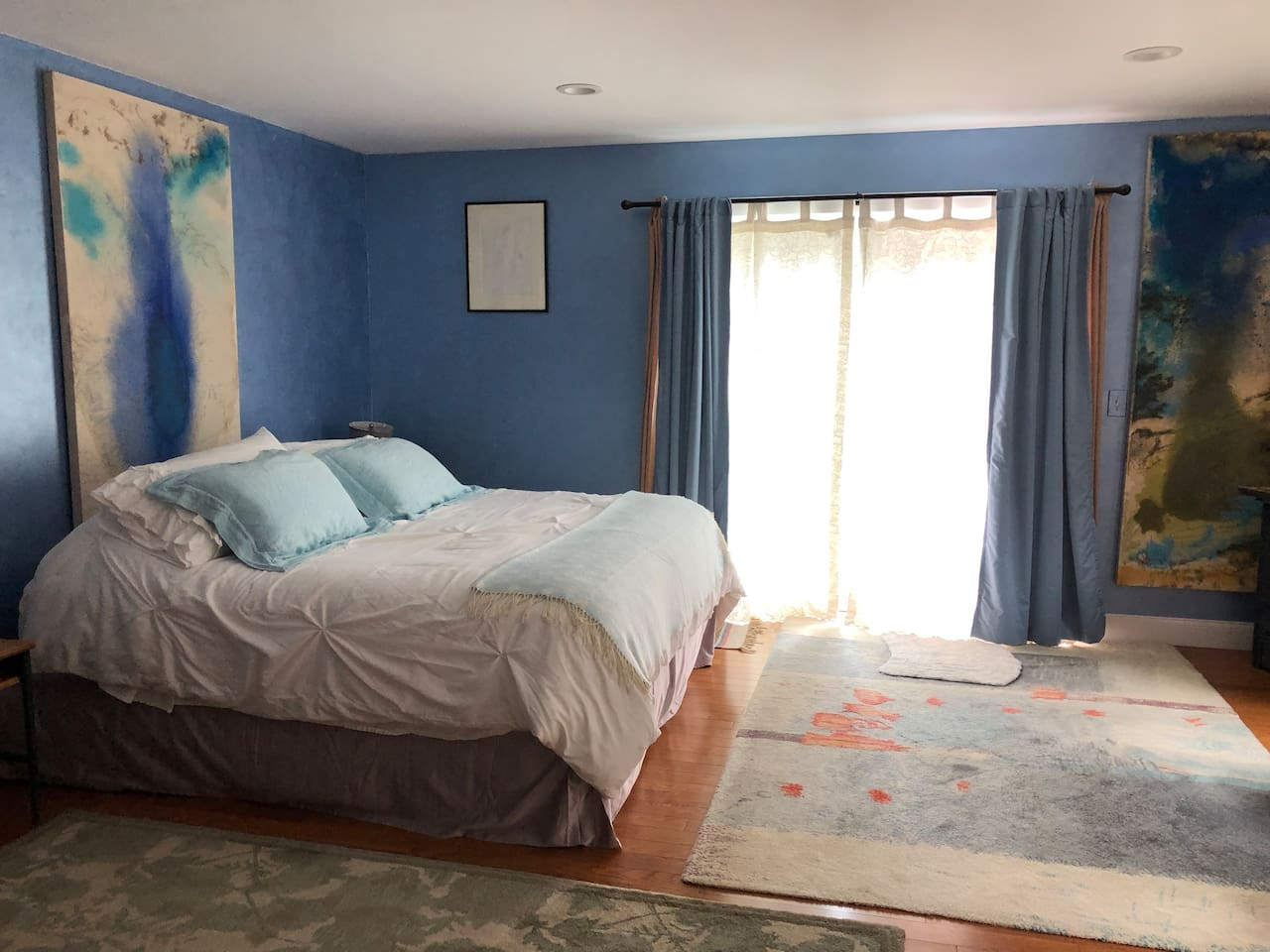 A very comfortable bed, king size.  Pillow choices...cotton sheets hung on the line to dry, finished in the dryer. Slider doors behind curtains open out to a private back yard, and use of 1st floor deck.
