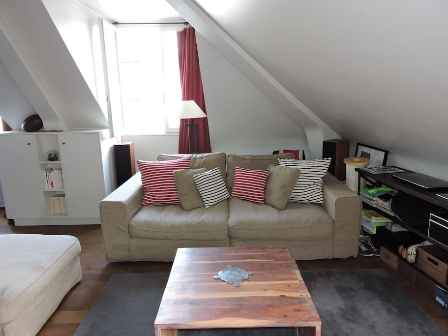 A comfortable couch under the attic which reveals the charm of the room