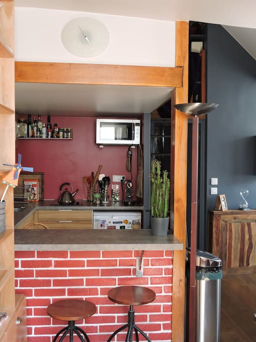 The fitted kitchen opened on the dining room by a red-bricks-bar