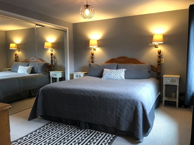 Master bedroom with comfy king bed and water view