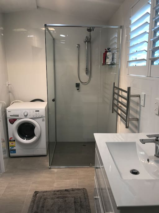 Washing machine , shower, vanity a window with shatters.