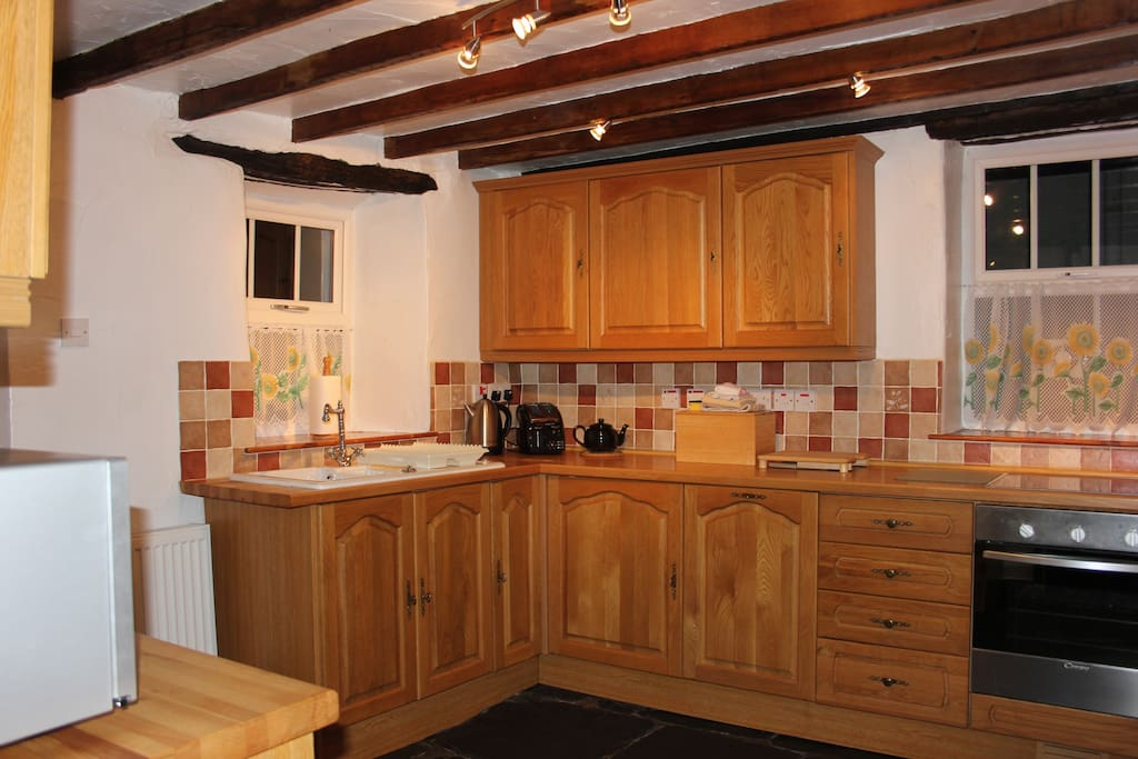 Fully fitted, well equipped integrated oak kitchen with original flagged floor and oak beams