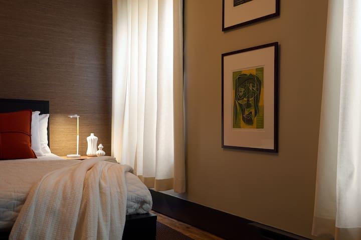 Queen bed in spacious suite.