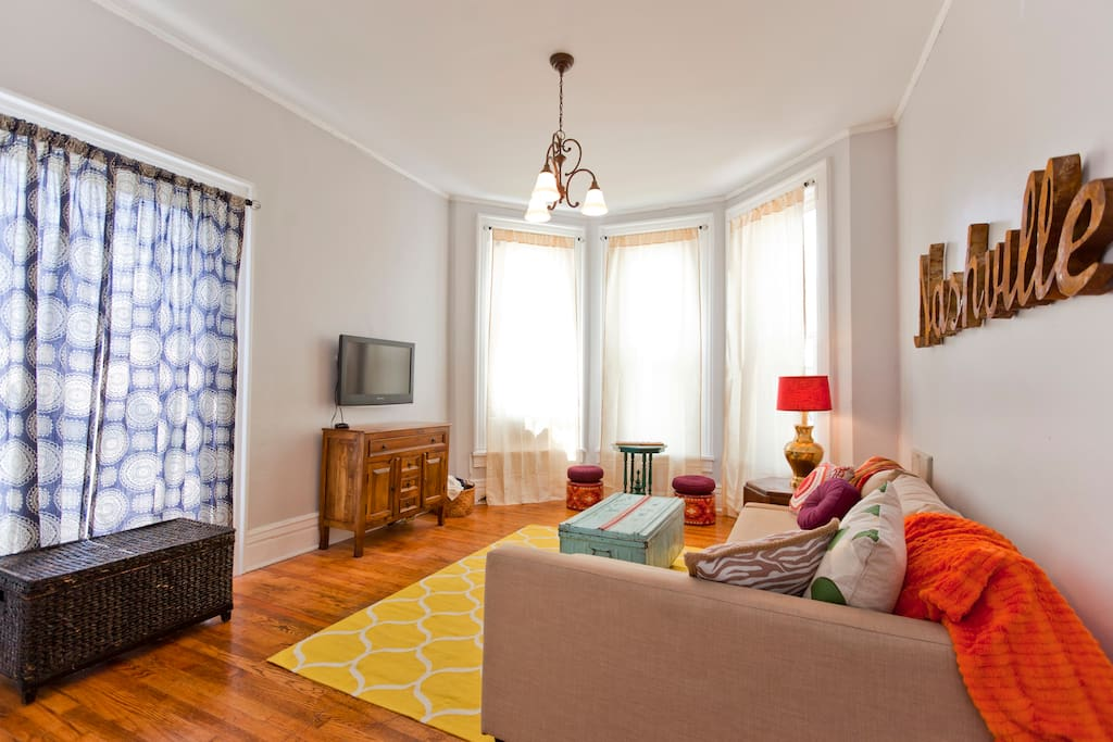 Living room with large bright windows facing Broadway