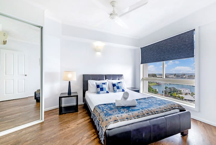 On the main level, a second bedroom is furnished with a queen bed and built-in mirrored wardrobes and has stunning marina views from an oversized window.