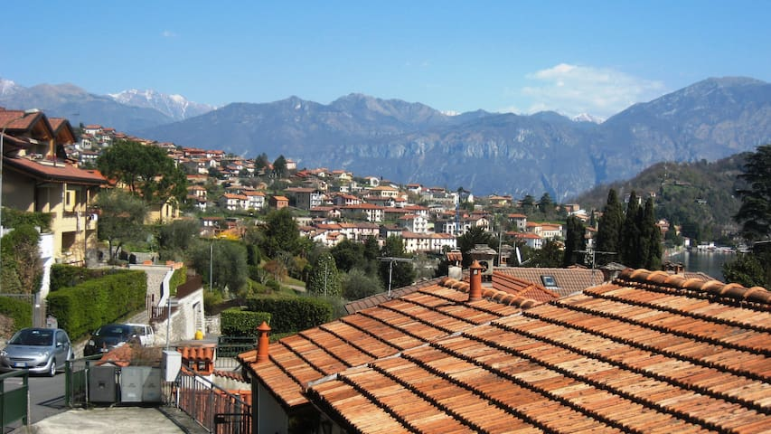 From across the road outside the studio, the view north along the Lake with car access via `Viale degli Ulivi` on the left