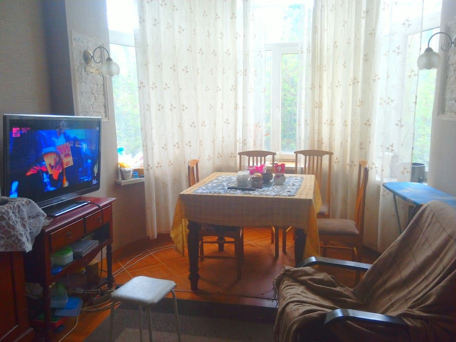 Кухня, имеется большой холодильник, кресло-качалка, раковина, стойка для приготовления еды, куллер, микроволновка и большой телевизор. Окна выходят во двор.