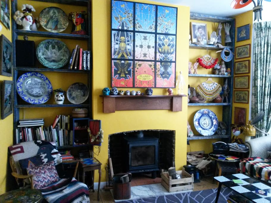 Wood stove fire in the living room filled with art, books, curios etc...