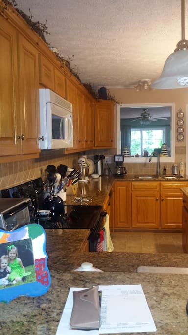 Kitchen has granite countertop, dishwasher, coffee pot and microwave.  Also has island.