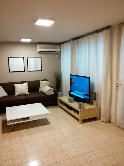 living area with air conditioning and cable big TV
