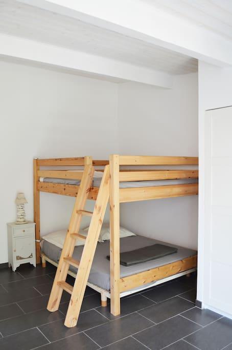 Deux lits superposés en 140 x 190 cm pour 2 adultes et 1 enfant.