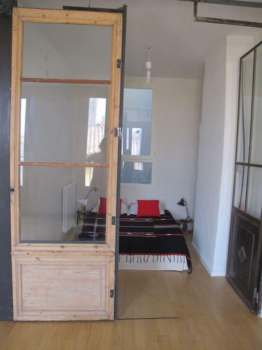 Une chambre à la cloison vitrée coulissante ouvrant sur un salon baigné de lumière