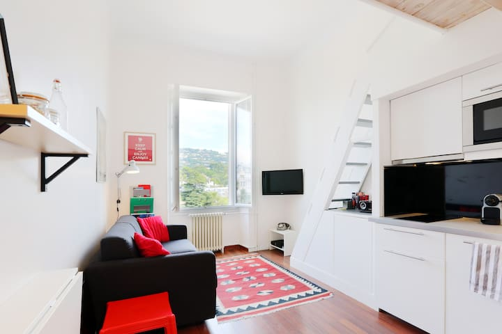 The Living has a comfortable sitting area with cable TV and internet. There is a full length window with a view over the hills of Cannes.