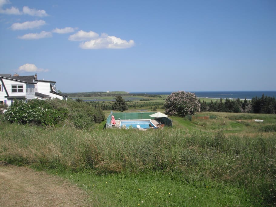 View of beach, house and pool from bench on property.
