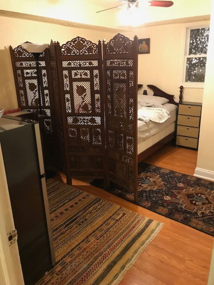 Your room--queen size bed, small fridge, two-person tall table/desk, closet, set of drawers, and you can collapse the wood screen if you prefer