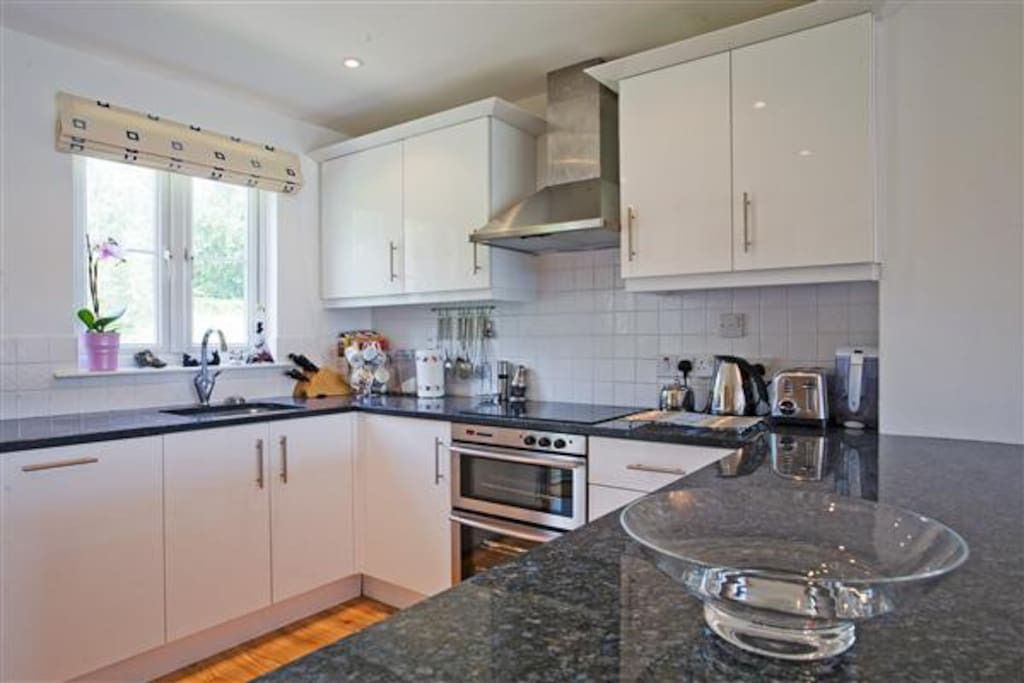 Modern well equipped kitchen with granite worktops, dishwasher, freezer, fridge and oven