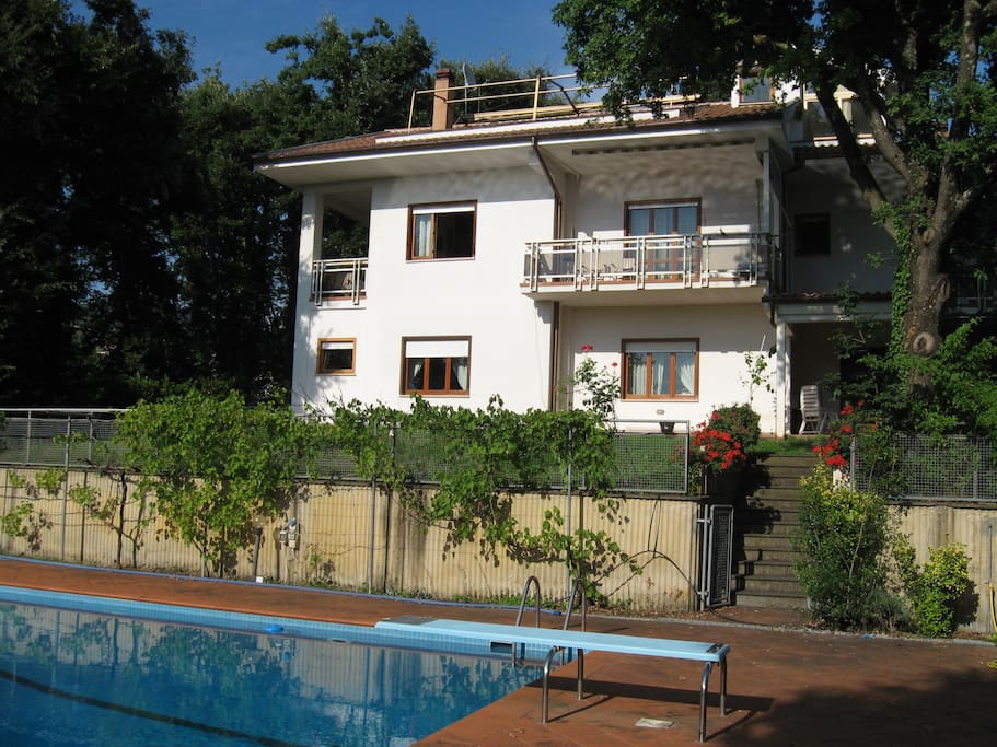 View of the villa surrounded by the garden and high-grown oak woodland, shot from the pool.