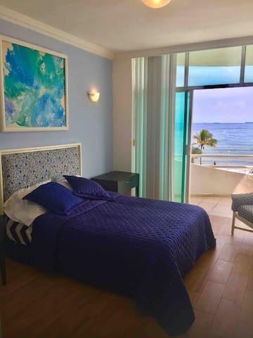 Recamara principal con baño privado, vista al mar y aire acondicionado, ideal para 2 huéspedes.