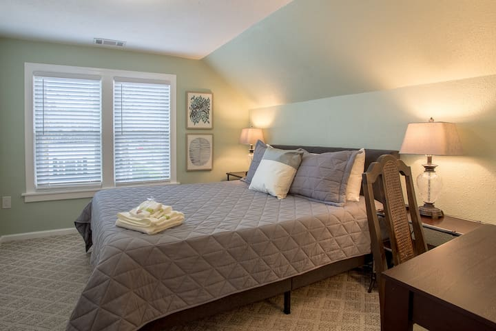 Entering the north facing master bedroom with luxury queen memory foam mattress includes desk with chair and charging station on Baker furniture nightstand. Extra blanket and down comforter on bed or in closet to adjust to your personal needs.