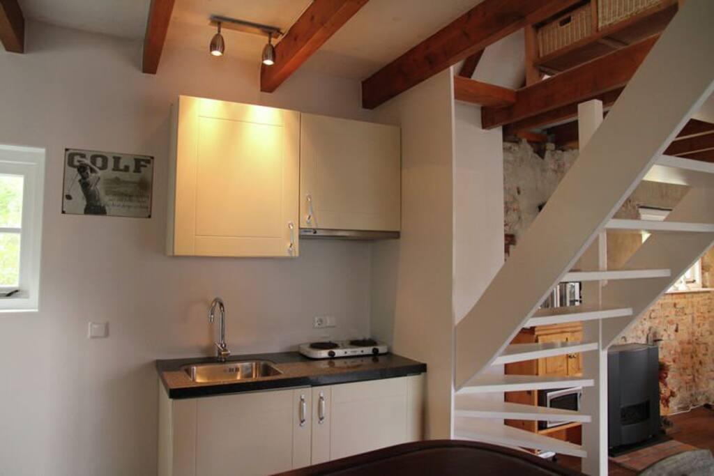 Kleine keuken voorzien van 2 pits elektrisch koken, koelkast tafelmodel en een magnetron. Koffiezetapparaat aanwezig
