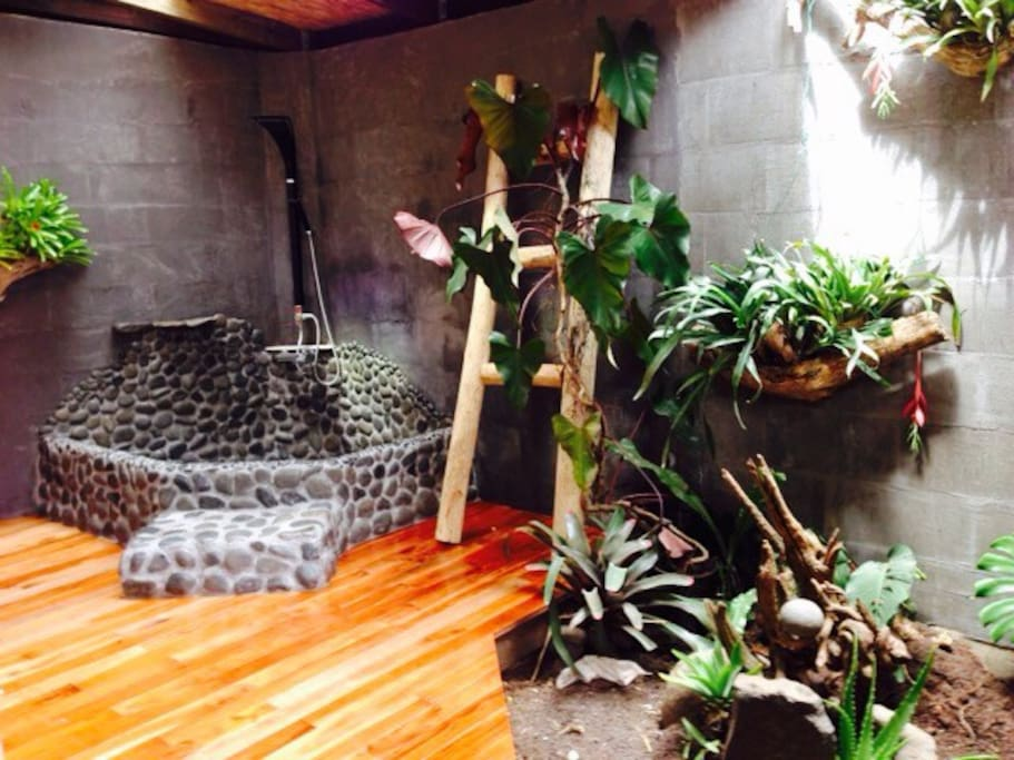 Lava rock bath with open roof and zen garden.