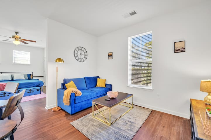 A vibrant blue couch with golden accents throughout the room, for a nice lux feel