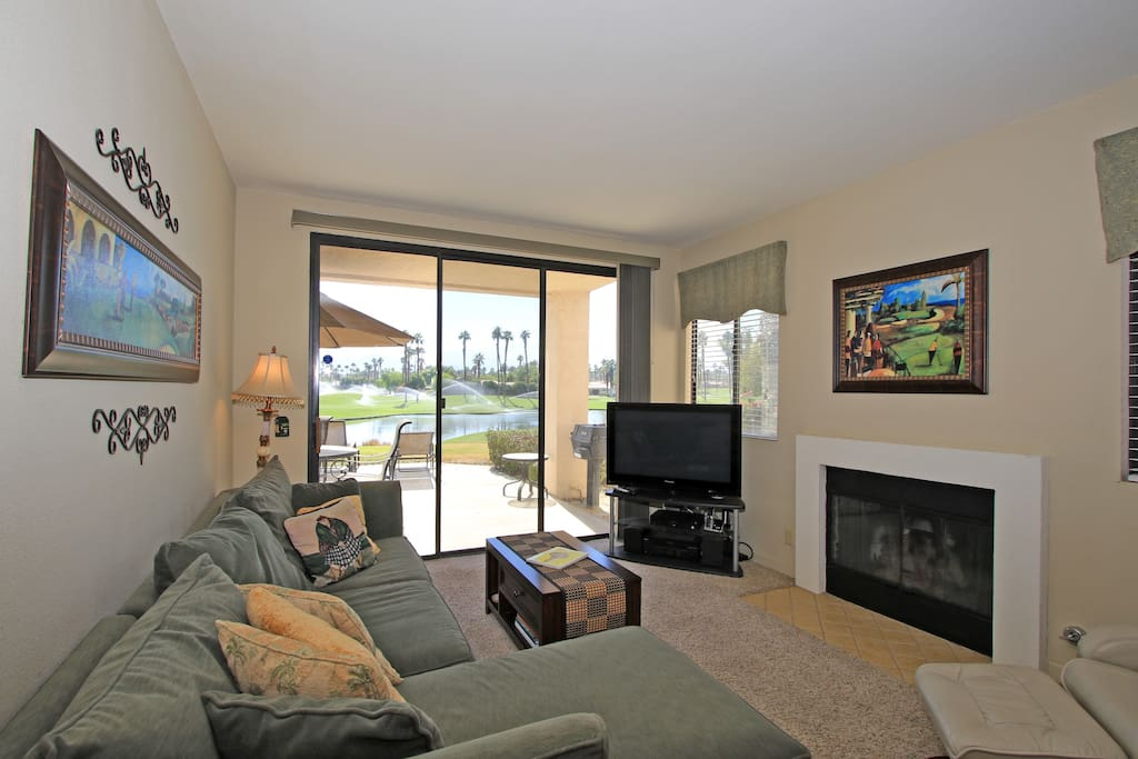 Living area with flat screen TV, gas fireplace and sliding glass doors to back patio