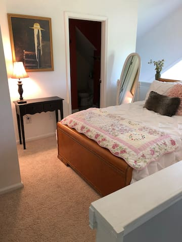 Loft full size bed shown with bathroom entrance