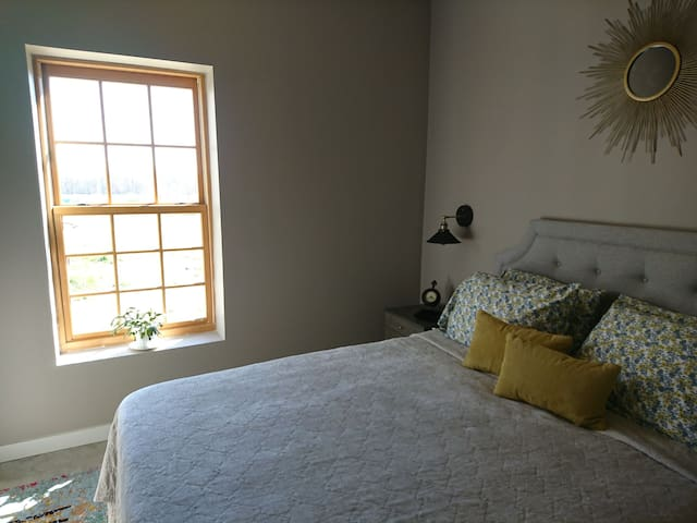 Bedroom has heated concrete flooring with an area carpet. On this nightstand there is a leather catch all and a small clock. The window lets in lots of sunshine and there is a black out shade to block out any light during the day or night.