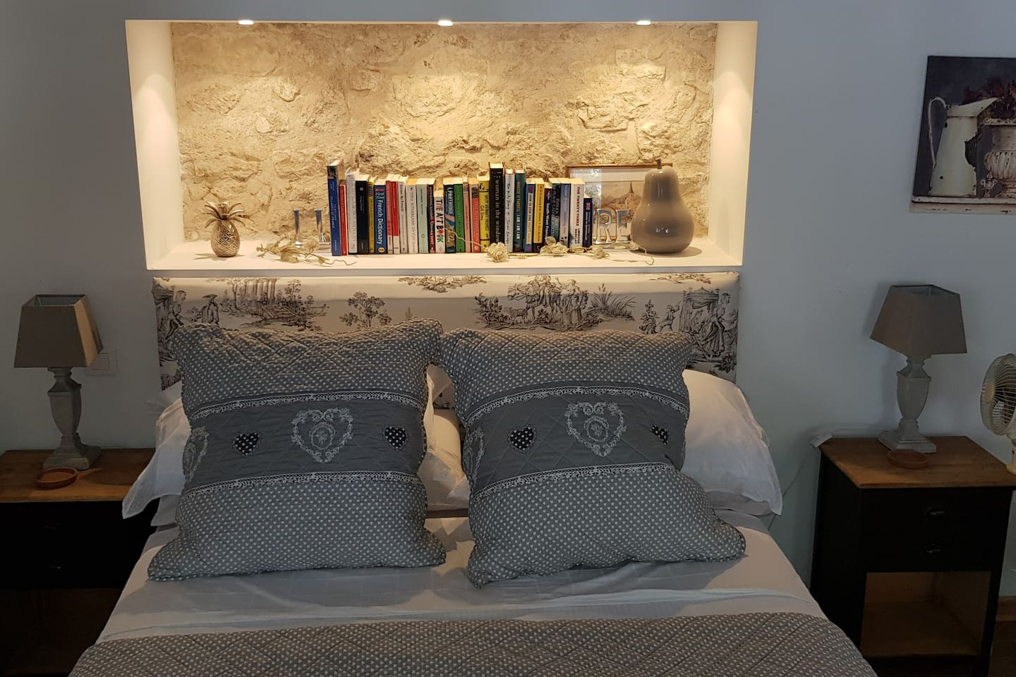 The double bed with recessed lighting and  feature wall.