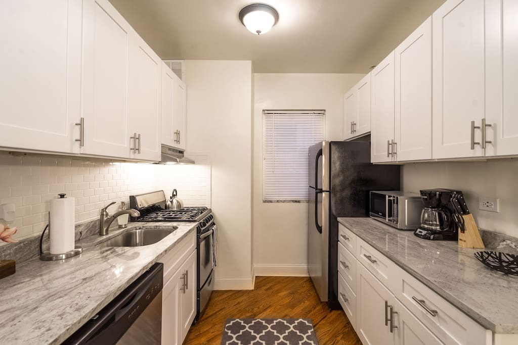 Kitchen - Stainless steel appliances, shaker-style cabinets, and white granite, equipped with essentials.